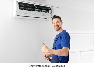 Male technician after successful repair of air conditioner indoors