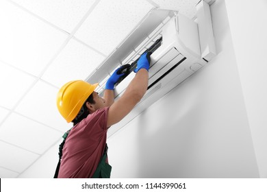 Male technician checking air conditioner indoors