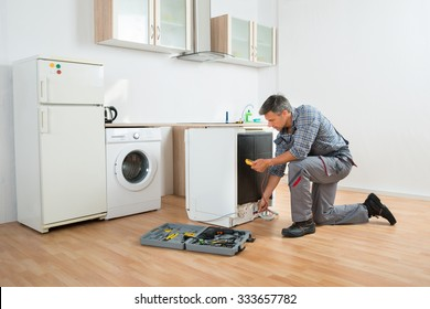 Male technician checking dishwasher with digital multimeter in kitchen