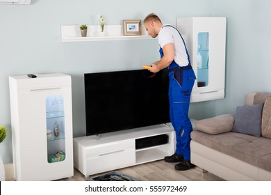 Male Technician Checking Television With Digital Multimeter