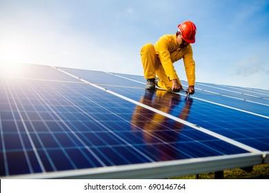 Male technician checks the maintenance of the solar panels.