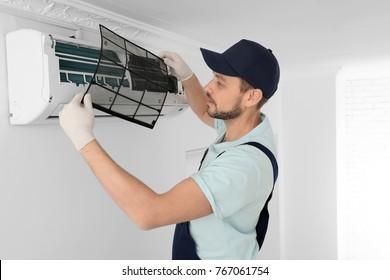 Technicien masculin nettoyant l'air conditionné à l'intérieur