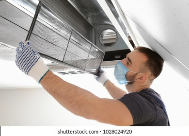 Male technician cleaning industrial air conditioner indoors - Shutterstock ID 1028024920