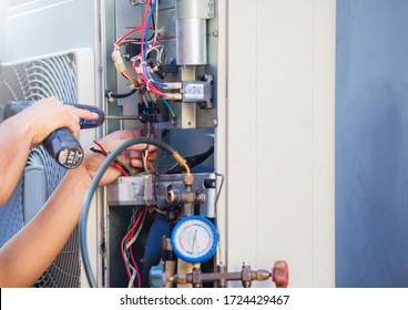 Male technician hands using a screwdriver fixing modern air conditioner, repairing and servicing, Maintenance and repairing concept