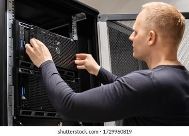 Male Technician Installing Servers In Enterprise Datacenter for Cloud Hosting