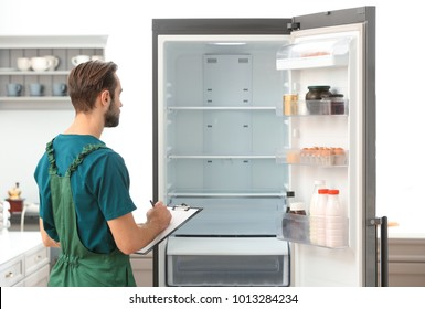 Male technician making notes during repair of refrigerator indoors