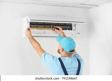 Male technician measuring air conditioner indoors
