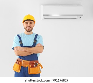 Male technician posing near air conditioner indoors