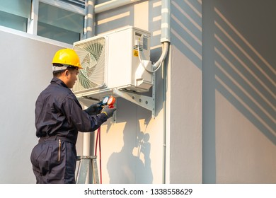 Male technician repairing air conditioner safety uniform, Technician vacuum pump evacuates and checking new air conditioner.