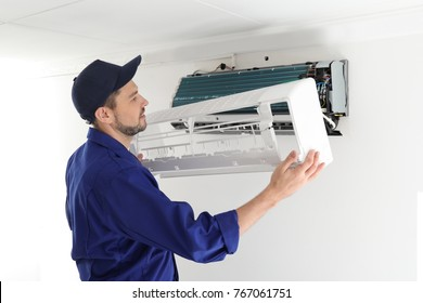 Male technician repairing air conditioner indoors