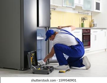 Male technician repairing broken refrigerator in kitchen