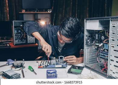 Male technician repairing computer hardware in the office. Repairman is trying to fix using the tools on the computer. Concept of repairing, upgrade, service, electronics and technology of computer.