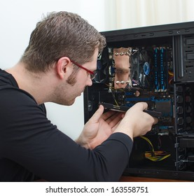 Male technician repairing computer at store