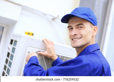 Male technician repairing conditioner outdoors