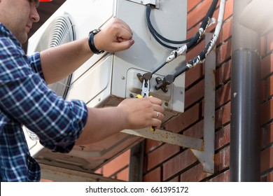 Male technician repairing outdoor air conditioner unit