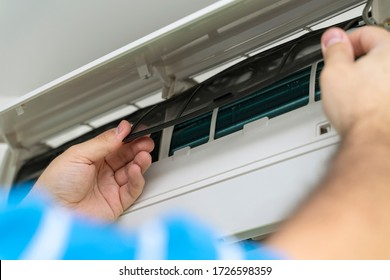 Male technician repairing and reading air conditioners. Opening the cover and cleaning the right filter