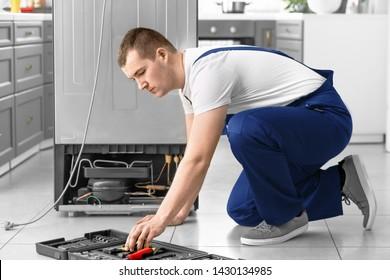 Male technician repairing refrigerator in kitchen
