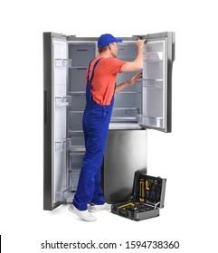 Male technician repairing refrigerator on white background