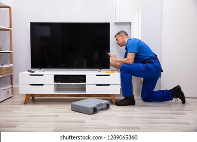 Male Technician Repairing Television With Digital Multimeter At Home