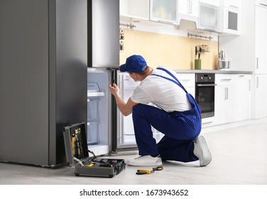 Male technician with screwdriver repairing refrigerator in kitchen