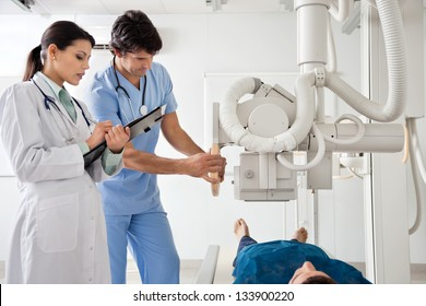 Male technician setting up machine to perform x-ray on patient while female radiologist noting down notes