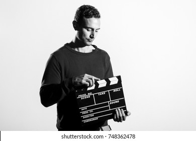 Male technician standing with a clapperboard. Indoors. Converted to black and white, grain added.