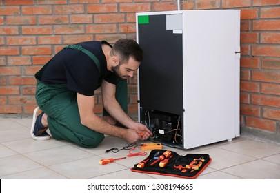 Male technician in uniform repairing refrigerator indoors