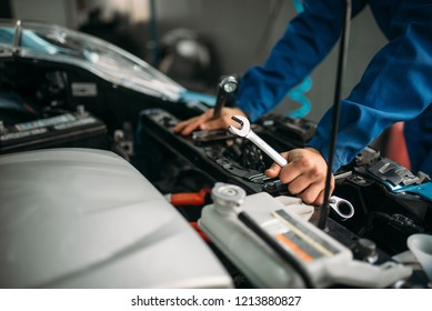 Male technician works with car engine