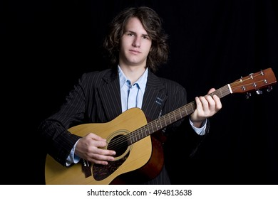 Male teenager folk guitar player with blank expression