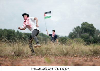 A male teenager wearing a keffiyeh to cover his face is throwing stones while his friend waving a Palestine flag at the background