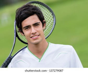 Male tennis player holding racket at the court