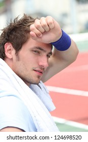 Male tennis player tired after match