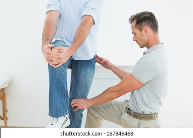 Male therapist assisting young man with stretching exercises in the medical office