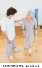 Male therapist in discussion with a disabled senior patient in the gym at hospital