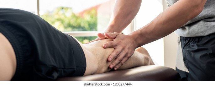 Male therapist giving leg massage to athlete patient on the bed in clinic for sports physical therapy concept, panoramic banner