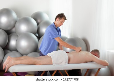 male therapist massaging middle age caucasian man' s back