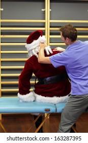 male therapist massaging stressed Santa Claus