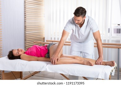 Male Therapist's Hand Massaging Woman's Leg In Clinic