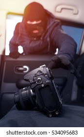 Male thief in black robbery mask stealing photo camera from car back seat
