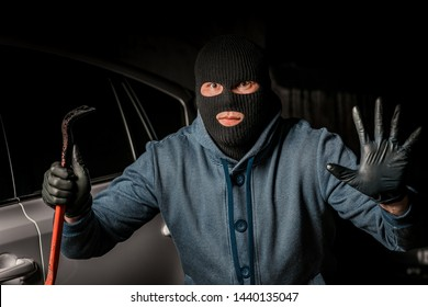 male thief is going to open the car door with a crowbar
