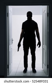 Male thief with gun entering the room