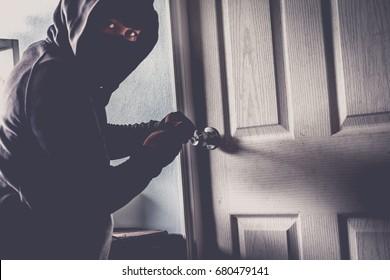Male thief opening door