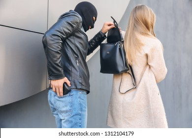 Male thief stealing wallet with money from woman outdoors