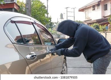 Male thief tries to steal a car. Car theft concept