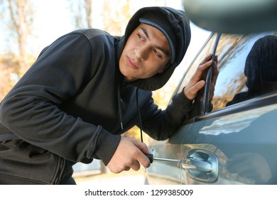 Male thief trying to open car