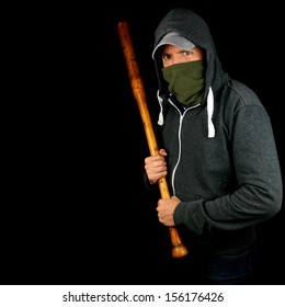 Male thug in hoodie waiting to attack with wooden baseball bat. Isolated on black background.