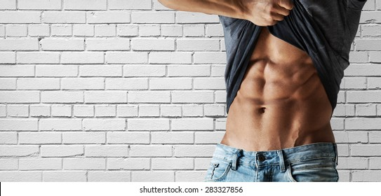 Male torso with diced press against a white brick wall
