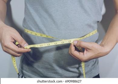 Male torso with measure tape on waistline .selective focus