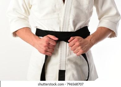 Male torso and sportive arms on white background. Guy poses in white kimono with black belt, close up. Karate fighter with fit strong hands gets ready to fight. Japanese karate and sports concept