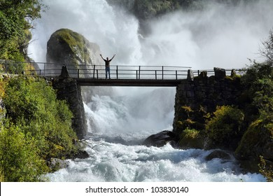Male tourist above an extremely powerful waterfall in Briksdalen valley, Jostedalsbreen National Park in Norway.